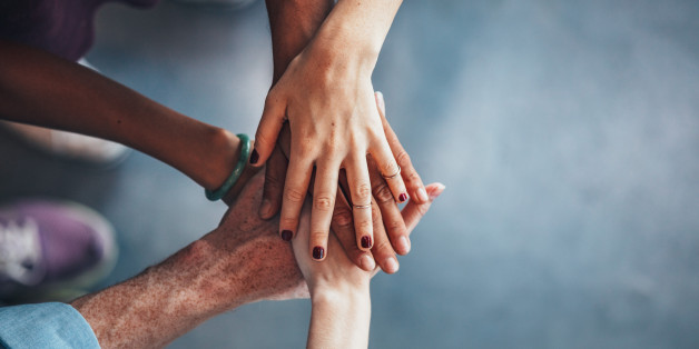 Multiethnic group of young people putting their hands on top of each other. Close up image of young students making a stack of hands.