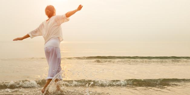 Carefree woman dancing in the sun on the beach