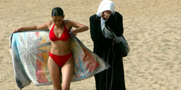 A young woman wearing a bikini walks along the beach with a friend in dressed in traditional clothes at the Palm Beach Club in Algiers July 25, 2003. [It is the summer of 2003 and the scars from a decade of Islamist extremist-linked violence that left between 100,000 and 150,000 people dead in the oil-rich north African country are almost no longer visible.] Temperatures soar above 40 degrees Celsius and people are back on Algeria's beaches escaping the town's heat and having fun.