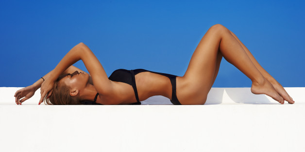 Sexy fashion model in swimwwear with skined body against blue sky on background