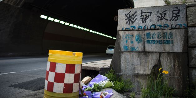 Flowers are placed at the entrance of the Taojiakuang tunnel in the city of Weihai in Shandong province on May 10, 2017. Eleven South Korean and Chinese kindergarteners and their driver were killed when a school bus crashed and burst into flames in a tunnel in eastern China on May 9, officials said. / AFP PHOTO / Johannes EISELE        (Photo credit should read JOHANNES EISELE/AFP/Getty Images)