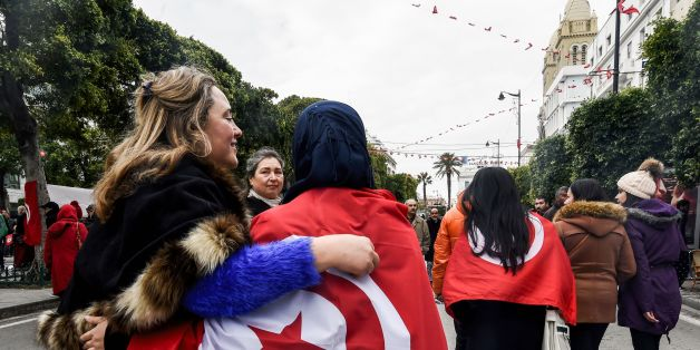 Two Tunisian women embrace as one wears the national flag, during a rally on January 14, 2017 in the Habib Bourguiba Avenue in the capital Tunis to mark the sixth anniversary of the 2011 revolution. / AFP / FETHI BELAID        (Photo credit should read FETHI BELAID/AFP/Getty Images)