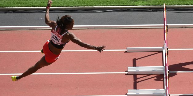 Trinidad and Tobago's Deborah John (L) falls as she competes in the women's 100m hurdles athletics event at the 2017 IAAF World Championships at the London Stadium in London on August 11, 2017. / AFP PHOTO / Glyn KIRK        (Photo credit should read GLYN KIRK/AFP/Getty Images)
