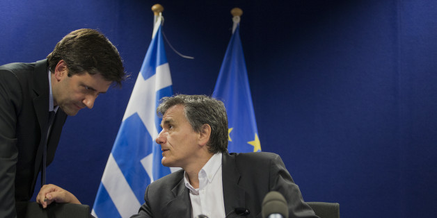 Euclid Tsakalotos, Greece's finance minister, right, speaks with a member of his team before the start of a press conference after a Eurogroup meeting in Brussels, Belgium, on Monday, May 9, 2016. The euro area and the International Monetary Fund will assess whether Greek Prime Minister Alexis Tsipras has made enough budget-tightening commitments to gain another disbursement of emergency loans. Photographer: Jasper Juinen/Bloomberg via Getty Images