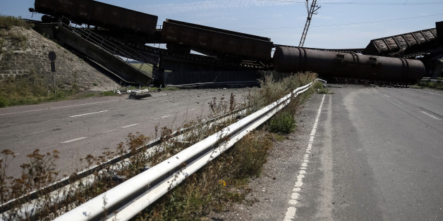 Train wagons are seen on the destroyed railway bridge which collapsed during the fighting between the Ukrainian army and pro-Russian separatists, over a main road leading to the eastern Ukrainian city of Donetsk, near the village of Novobakhmutivka, north of Donetsk city, August 27, 2014.  REUTERS/Gleb Garanich  (UKRAINE - Tags: POLITICS CIVIL UNREST TRANSPORT)