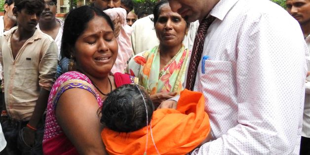 TOPSHOT - EDITORS NOTE: Graphic content / Relatives mourn the death of a child at the Baba Raghav Das Hospital in Gorakhpur, in the northern Indian state of Uttar Pradesh, on August 12, 2017.At least 60 children have died over five days at a government hospital in northern India that suffered oxygen shortages, officials said August 12 amid fears the toll could rise. Authorities said they have launched an inquiry but denied reports that a lack of oxygen had caused the deaths at the Baba Raghav Da