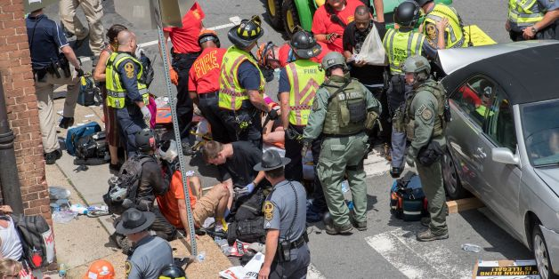 People receive first-aid after a car accident ran into a crowd of protesters in Charlottesville, VA on August 12, 2017. A picturesque Virginia city braced Saturday for a flood of white nationalist demonstrators as well as counter-protesters, declaring a local emergency as law enforcement attempted to quell early violent clashes. / AFP PHOTO / PAUL J. RICHARDS        (Photo credit should read PAUL J. RICHARDS/AFP/Getty Images)