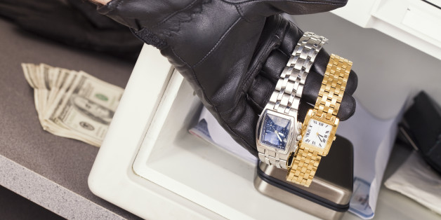 The gloved hand of a thief who is stealing watches and cash from a safe.