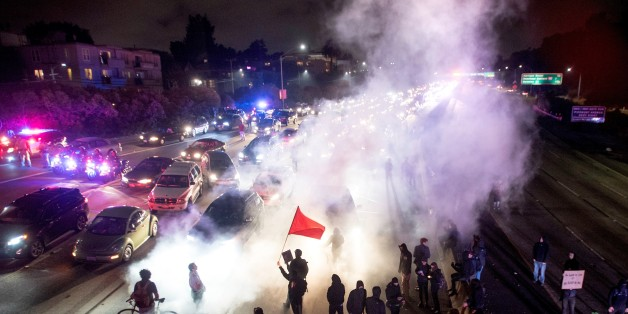 TOPSHOT - Protesters block both directions of the Interstate 580 freeway during a rally against racism in Oakland, California on August 12, 2017. Protesters marched on the streets of Oakland in response to a series of violent clashes that erupted at a white-nationalist rally in Charlottesville, Virginia earlier in the day that left at least one dead and dozens injured. / AFP PHOTO / Josh Edelson        (Photo credit should read JOSH EDELSON/AFP/Getty Images)