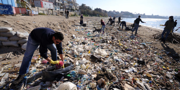 Volunteers collect trash on Tamentfoust beach on January 20, 2012, east of Algiers, during a clean-up operation. AFP PHOTO/FAROUK BATICHE (Photo credit should read FAROUK BATICHE/AFP/Getty Images)