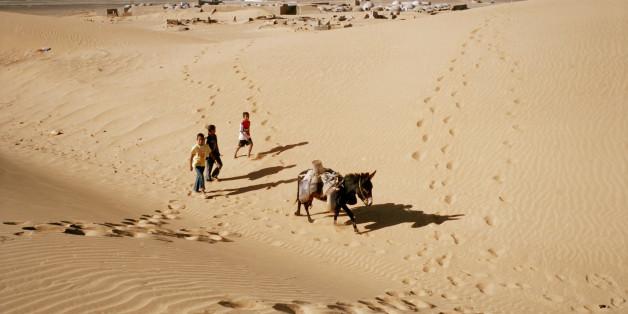 TINDOUF, ALGERIA - FEBRUARY 2:  Sahrawi children carry water with a donkey through the Sahara Desert near the Sahrawi refugee camp in Dakhla on February 2, 2012 in Tindouf, Algeria. (Photo by Stefano Montesi/Corbis via Getty Images)