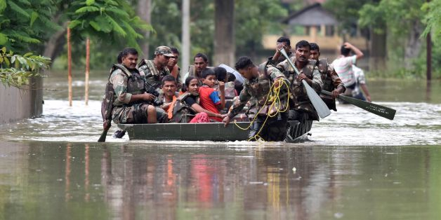 Indian army soldiers evacuate villagers in the flood affected Jakhalabandha area in Koliabor, some 186km from Guwahati, the capital city of Indias northeastern state of Assam on August 13, 2017. / AFP PHOTO / Biju BORO        (Photo credit should read BIJU BORO/AFP/Getty Images)