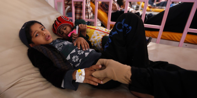 A Yemeni woman holds the hand of one of her children, who is suspected of being infected with cholera, as they receive treatment at a hospital in the capital Sanaa, on August 12, 2017.A cholera outbreak has claimed the lives of some 2,000 Yemenis in less than four months. / AFP PHOTO / Mohammed HUWAIS        (Photo credit should read MOHAMMED HUWAIS/AFP/Getty Images)