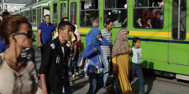 People walk past trams in the streets of the capital Tunis October 22, 2014. Tunisians go to the polls on October 26 for their second free parliamentary election. Presidential elections will follow next month.  REUTERS/Anis Mili (TUNISIA - Tags: ELECTIONS POLITICS TRANSPORT)