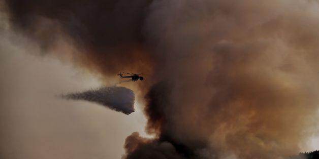 A firefighting helicopter drops waters over a fire, east of the Greek capital Athens on August 15, 2017. 