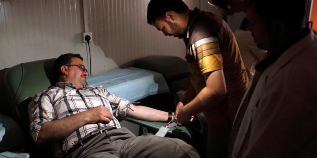 An Iraqi hospital staff member prepares a man for blood donation at Ibn al-Atheer hospital in eastern Mosul, Iraq, May 13, 2017. REUTERS/Danish Siddiqui