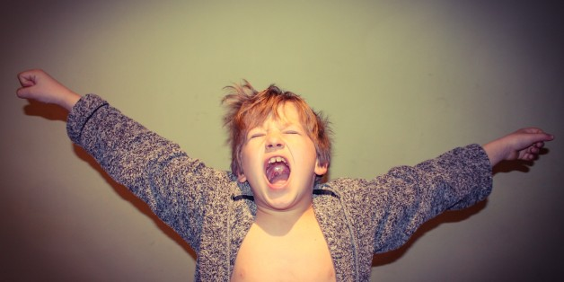Young boy having a large stretch and yawn