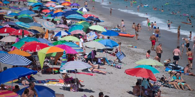 People sunbathe on the Burriana beach in Nerja, near Malaga, on August 12, 2017. / AFP PHOTO / JORGE GUERRERO        (Photo credit should read JORGE GUERRERO/AFP/Getty Images)