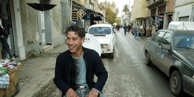 ALGER, ALGERIA:  Algerian Sofiane, 18, guards parked cars in the street of Algier 11 December 2003. The rise of the number of cars in big Algerian cities benefits to young unemployed who have taken over the streets and established themselves as 'parking guards'.     AFP PHOTO HOCINE ZAOURAR  (Photo credit should read HOCINE ZAOURAR/AFP/Getty Images)