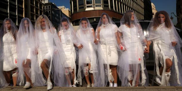 Activists from the Lebanese NGO Abaad (Dimensions), a resource centre for gender equality, dressed as brides and wearing injury patches hold a protest in downtown Beirut on December 6, 2016, against article 522 in the Lebanese penal code.  The article shields rapists from prosecution on the condition that they marry their victim, a phenomenon that is still practised in the country, especially among conservative families whose chief aim is to preserve the family's so-called 'honour.' / AFP / PATRICK BAZ        (Photo credit should read PATRICK BAZ/AFP/Getty Images)