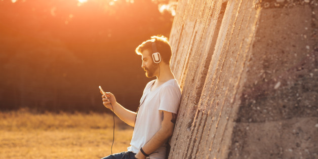 Hipster boy leaning on a wall and listening to music on his mobile phone