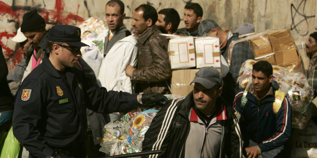 A Spanish policeman speaks to a Moroccan man at the border between Spain and Morocco in Ceuta January 31, 2008. Many Moroccan people cross the border to buy Spanish products in Ceuta to sell in Morocco. REUTERS/Rafael Marchante (SPAIN)