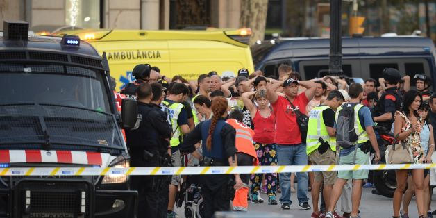 Policemen check the identity of people standing with their hands up after a van ploughed into the crowd, killing two persons and injuring several others on the Rambla in Barcelona on August 17, 2017. A driver deliberately rammed a van into a crowd on Barcelona's most popular street on August 17, 2017 killing at least two people before fleeing to a nearby bar, police said.  Officers in Spain's second-largest city said the ramming on Las Ramblas was a 'terrorist attack' and a police source said one suspect had left the scene and was 'holed up in a bar'. The police source said they were hunting for a total of two suspects. / AFP PHOTO / Josep LAGO        (Photo credit should read JOSEP LAGO/AFP/Getty Images)