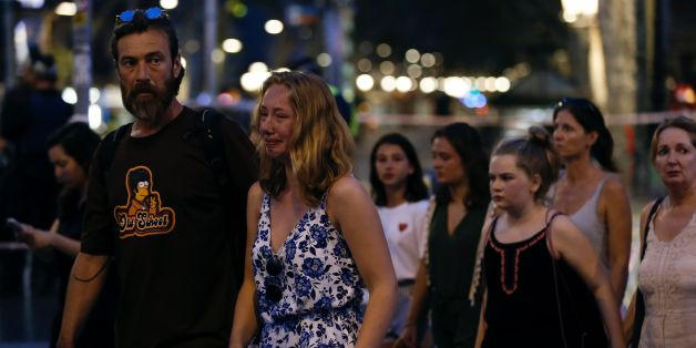 A woman cries as she and others are escorted by Spanish policemen outside a cordoned off area after a van ploughed into the crowd, killing 13 persons and injuring over 80 on the Rambla in Barcelona on August 17, 2017.A driver deliberately rammed a van into a crowd on Barcelona's most popular street on August 17, 2017 killing at least 13 people before fleeing to a nearby bar, police said. Officers in Spain's second-largest city said the ramming on Las Ramblas was a 'terrorist attack'. / AFP PHOTO