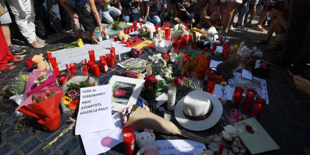People stand next to flowers, candles, a sign reading ' Out terrorism and attacks, we want peace' and other items set up on the Las Ramblas boulevard in Barcelona as they pay tribute to the victims of the Barcelona attack, a day after a van ploughed into the crowd, killing 13 persons and injuring over 100 on August 18, 2017.