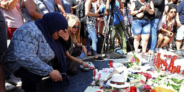 People gather next to flowers, candles and other items set up on the Las Ramblas boulevard in Barcelona as they pay tribute to the victims of the Barcelona attack, a day after a van ploughed into the crowd, killing 13 persons and injuring over 100 on August 18, 2017.Police hunted for the driver who rammed a van into pedestrians on an avenue crowded with tourists in Barcelona, leaving 13 people dead and  more than 100 injured, just hours before a second assault in a resort along the coast. / AFP