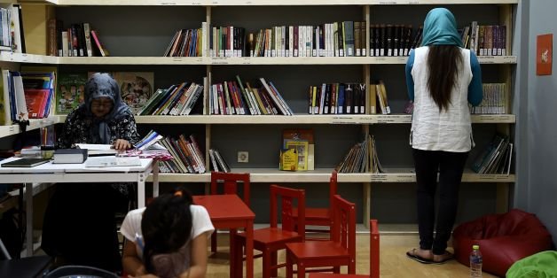 Refugees read books at a library set up on the premises of an international non-governmental organisation (NGO) hosting Syrian and Afghan women and children, in central Athens on August 17, 2017.There are increasingly initiatives in Greece to offer reading and books to the tens of thousands of refugees stranded in the country. / AFP PHOTO / ARIS MESSINIS        (Photo credit should read ARIS MESSINIS/AFP/Getty Images)