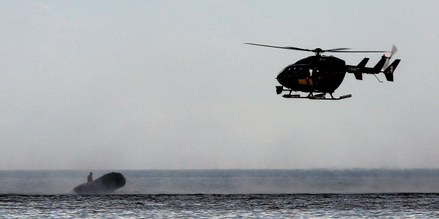 A Frontex helicopter stops a dinghy with a suspected smuggler off the Greek island of Lesbos September 24, 2015. According to witnesses, earlier the dinghy ferried Afghan migrants on a beach in Lesbos. On its way back to Turkish coast, the suspected smuggler was stopped by a Frontex chopper and arrested by the crew of a Greek Coast Guard vessel.  REUTERS/Yannis Behrakis