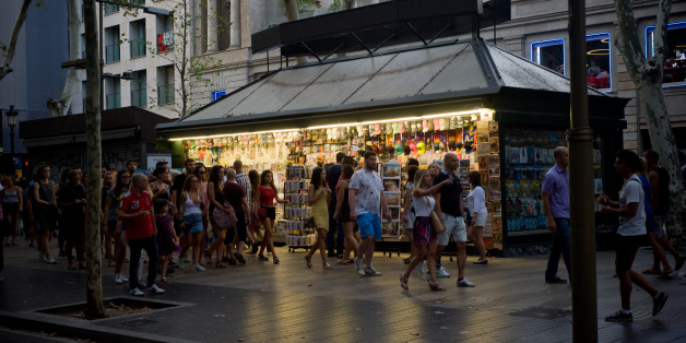 People walk past a kiosk  in Las Ramblas of Barcelona, Spain, on 18 August 2017,  a day after a van ploughed into the crowd, killing 14 persons and injuring over 100. (Photo by Jordi Boixareu/NurPhoto via Getty Images)