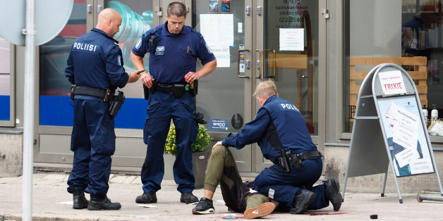TOPSHOT - Police officers detain a suspect, in the Finnish city of Turku where several people were stabbed, on August 18, 2017. Several people were stabbed in the southwestern Finnish city of Turku, police said after shooting and arresting a suspect. Public television station Yle reported that central Turku was on lockdown, with witnesses saying they had seen bodies lying on the ground in a busy area of the town. Businesses were shut. / AFP PHOTO / Kirsi Kanerva        (Photo credit should read