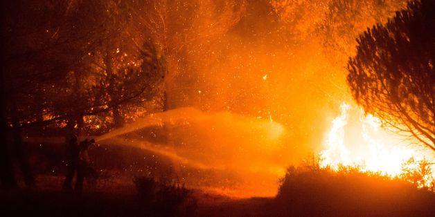 Firefighters work to put out a wildfire on a fire in Carnoux-en-Provence, southeastern France, on August 19, 2017. Vacationers who were staying near Aubagne were momentarily evacuated on the night of August 19 and residents confined to their homes as a wildfire burned through 200 hectares of vegetation, the Bouches-du-Rhone prefecture said. / AFP PHOTO / BERTRAND LANGLOIS        (Photo credit should read BERTRAND LANGLOIS/AFP/Getty Images)