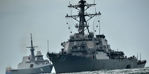 The guided-missile destroyer USS John S. McCain (R), with a hole on its portside after a collision with an oil tanker, is escorted by Singapore Navy RSS Intrepid (L) to Changi naval base in Singapore on August 21, 2017. Ten US sailors were missing and five injured after their destroyer collided with a tanker east of Singapore early Monday, the second accident involving an American warship in two months. / AFP PHOTO / Roslan RAHMAN        (Photo credit should read ROSLAN RAHMAN/AFP/Getty Images)