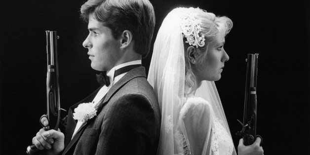 1980s BRIDE AND GROOM STANDING BACK TO BACK HOLDING DUELING PISTOLS  (Photo by H. Armstrong Roberts/ClassicStock/Getty Images)