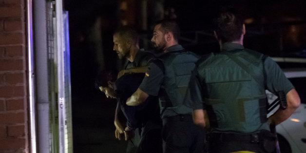 La police espagnole escorte un des suspects arrêtés à Barcelone la semaine dernière