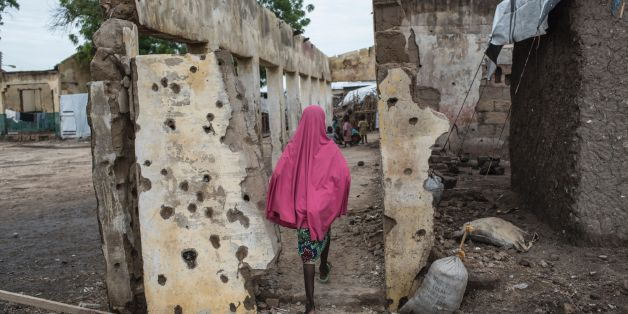 TOPSHOT - A girl walks through the site where the Nigerian Air Force (NAF) mistakenly bombed the Rann Internally-Displaced Peoples (IDP) camp in northeastern Nigeria near the Cameroonian border on July 29, 2017.On January 17, 2017 the Rann Internally-Displaced Persons (IDP) camp was bombed by the Nigerian Air Force (NAF), injuring hundreds of people, killing dozens of civilians and at least six humanitarian workers, in the mistaken belief that the large congregation of people was a Boko Haram mi