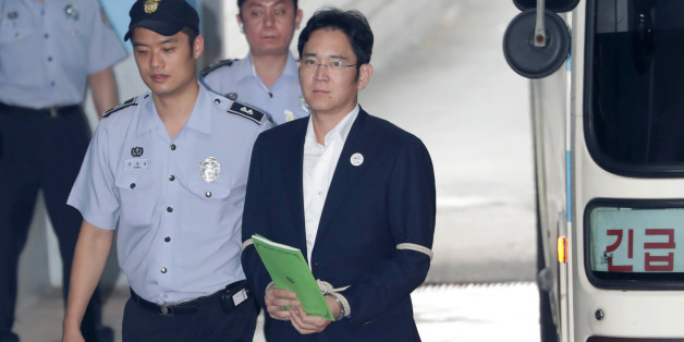 Jay Y. Lee, co-vice chairman of Samsung Electronics Co., right, is escorted by a prison officer as he arrives at the Seoul Central District Court in Seoul, South Korea, on Monday, Aug. 7, 2017. Lee last week rejected allegations that he paid bribes to a friend of South Koreas former president to secure support for a key merger. Photographer: Lee Young-ho/Pool via Bloomberg