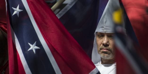 A member of the Ku Klux Klan looks on during a rally, calling for the protection of Southern Confederate monuments, in Charlottesville, Virginia on July 8, 2017.The afternoon rally in this quiet university town has been authorized by officials in Virginia and stirred heated debate in America, where critics say the far right has been energized by Donald Trump's election to the presidency. / AFP PHOTO / ANDREW CABALLERO-REYNOLDS        (Photo credit should read ANDREW CABALLERO-REYNOLDS/AFP/Getty