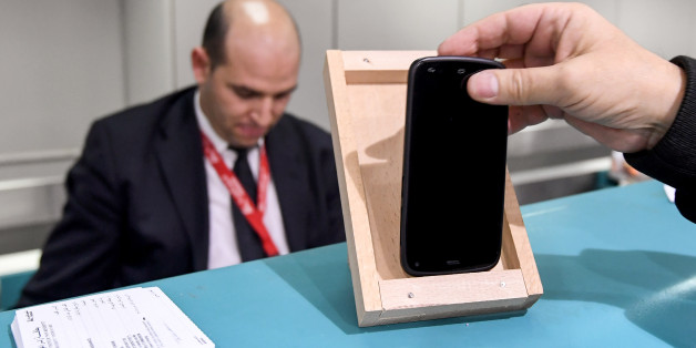 A Tunisian traveller measures the size of his cell phone in a frame on the check-in counter to be cleared for boarding his London-bound flight at Tunis-Carthage International Airport, on March 25, 2017. The United States this week announced a ban on all electronics larger than a standard smartphone on board direct flights out of eight countries across the Middle East, in effect from March 25, 2017. US officials would not specify how long the ban will last, but Emirates told AFP that it had been instructed to enforce the measures until at least October 14. Britain has also announced a parallel electronics ban targeting all flights out of Egypt, Turkey, Jordan, Saudi Arabia, Tunisia and Lebanon. / AFP PHOTO / FETHI BELAID        (Photo credit should read FETHI BELAID/AFP/Getty Images)