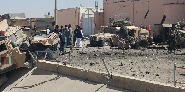 Afghan security personnel inspect the site of a suicide attack near the main police headquarters in Lashkar Gah, capital of Helmand province, on August 23, 2017. A Taliban suicide bomber killed five people and wounded dozens of others, mainly children as young as five, when he detonated a car packed with explosives at a police headquarters in southern Afghanistan on August 23. / AFP PHOTO / STR        (Photo credit should read STR/AFP/Getty Images)