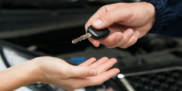 Closeup Of Mechanic Giving Car Key To Customer At Garage