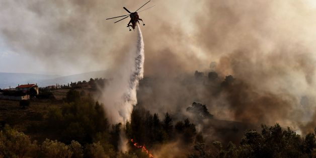 TOPSHOT - A firefighting helicopter drops water on a fire burning east of the Greek capital Athens on August 15, 2017. The army was called in to assist firefighters around Kalamos, 45 kilometres (30 miles) east of Athens, where a fire has been burning since August 13. In all, 146 fires have broken out across Greece since then according to authorities.    / AFP PHOTO / ARIS MESSINIS        (Photo credit should read ARIS MESSINIS/AFP/Getty Images)
