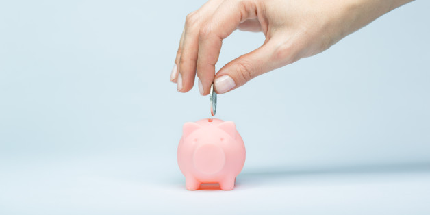 Female hand putting a coin into piggy bank. Light blue background, soft shadow. Canon 5D MK III