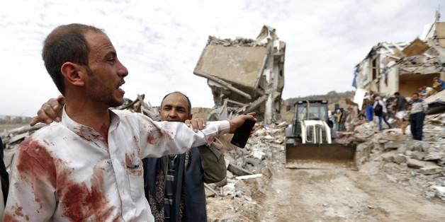 Un homme yéménite couvert de tâches de sang devant des débris de batiments bombardés à Sanaa, le 25 août 2017