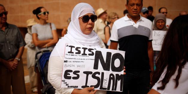 """Une femme tient une pancarte """"Daech n'est pas l'islam"""" lors d'un rassemblement à Fuengirola (Espagne) en solidarité avec les victimes de l'attaque terroriste de Barcelone, 20 août 2017."""