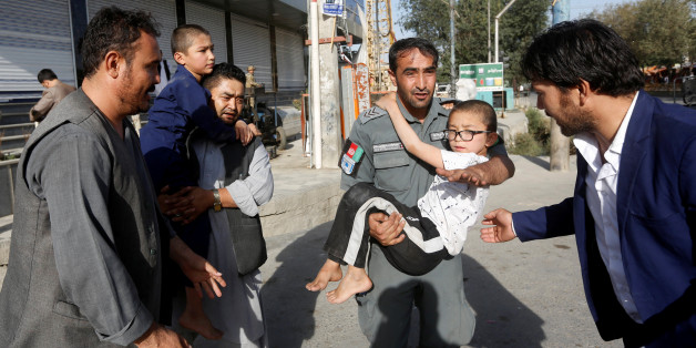Afghan policeman carries a boy rescued after a suicide attack followed by a clash between Afghan forces and insurgents, attack on a Shi'ite Muslim mosque in Kabul, Afghanistan, August 25, 2017. REUTERS/Omar Sobhani