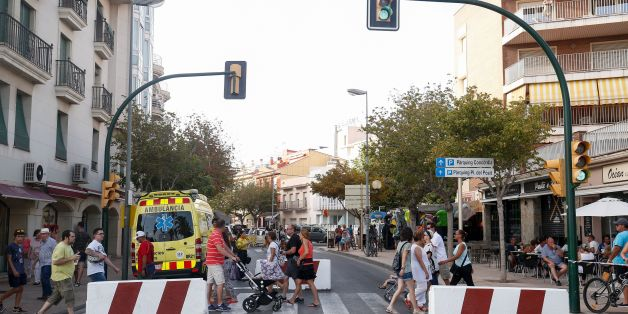 People walk past concrete barriers displayed to avoid vehicles to go through before a protest against terrorism in Cambrils following Barcelona and Cambrils attacks on August 25, 2017, one week after a van ploughed into the crowd, killing 13 persons and injuring over 100.